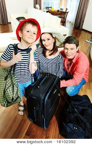 The family at home with a big suitcases.