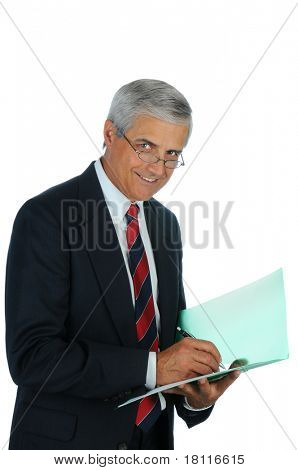 Portrait of a smiling middle aged business man writing in a file folder. Vertical format isolated on white.