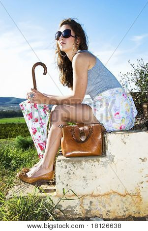 Young Woman With Handbag And Umbrella Sitting On Old Rustic Stairs