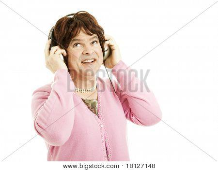 Cross dressing celebrity impersonator listening to headphones.   Isolated on white.