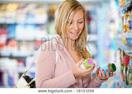 Closeup of a young woman smiling while holding jar in the supermarket