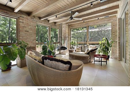 Sunroom in luxury home with wicker furniture