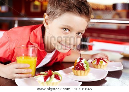 Portrait of cute lad with glass of juice and tasty cupcakes in cafe