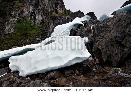 Ice blocks among rocks in mountains. Wild nature. East Sayan Mountains. Buryat Republic. Russia.