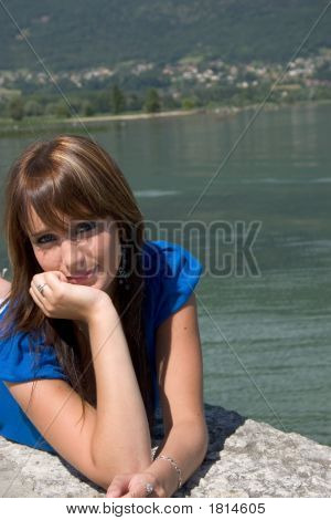 Woman Lengthened At The Edge Of A Lake