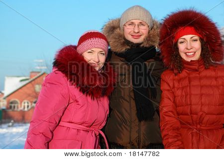 man and two women standing on outdoors in winter near to house, friends
