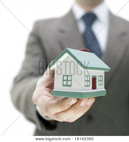 Real estate agent holding a toy house