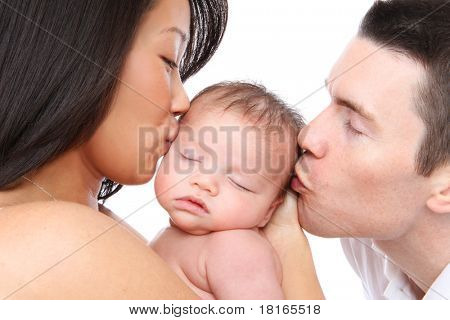 A mom and dad parent kissing their young baby