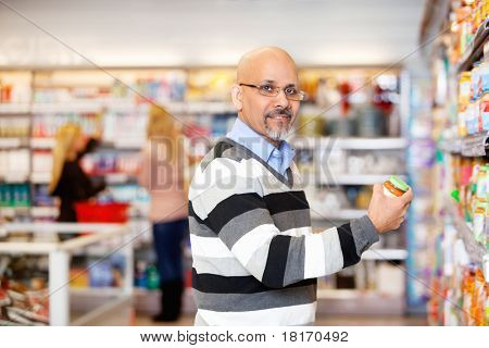 Portrait of a mature man shopping in the supermarket with people in the background
