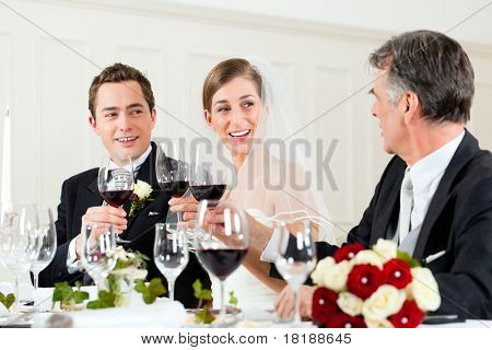 Wedding party at dinner - Bridal couple with father of bride