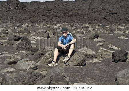 Boy Sitting On A Stone On An  Vulcanic Beach
