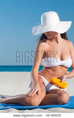 Beautiful young woman applying protective lotion before sunbathing at beach