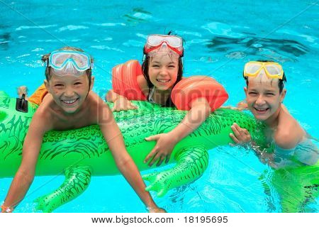 Closeup of smiling young brothers and sister in swimming pool with inflatable toy.