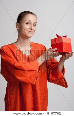 Smiling Girl In An Orange Background With A Gift Of Clothes In Hands Of