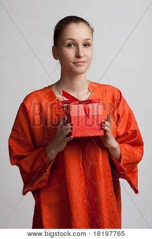 Girl In Orange Dress With A Gift In The Hands Of