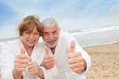 Happy senior couple on spa resort beach