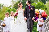 Wedding couple bride and groom with flower children or bridesmaid in white dress and flower baskets poster