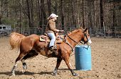stock photo of barrel racing  - A young woman turns around a barrel and heads to the finish line - JPG