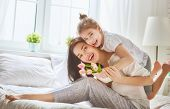 Happy mothers day! Child daughter congratulates mom and gives her flowers tulips and postcard. Mum  poster