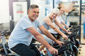 Confident seniors on exercise bikes  poster