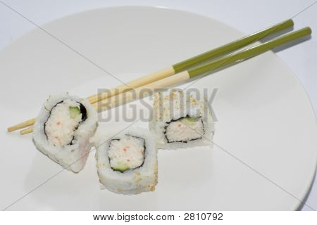 Three California Maki Sushi Rolls With Chopsticks