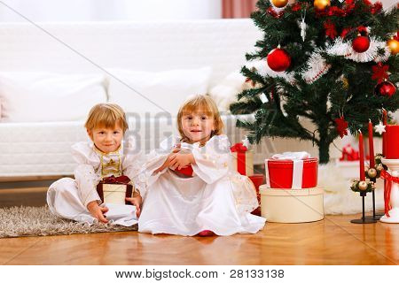 Two Happy Twins Girl Sitting With Presents Under Christmas Tree