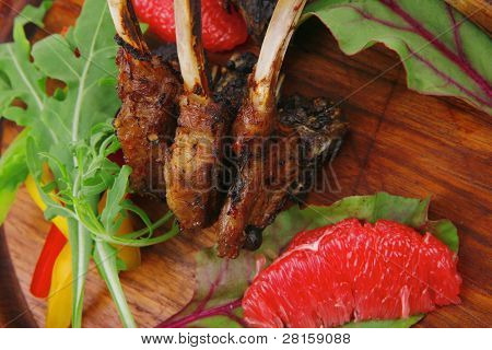 meat food : roast ribs on wooden plate with rocket leaves and grapefruit isolated over white background