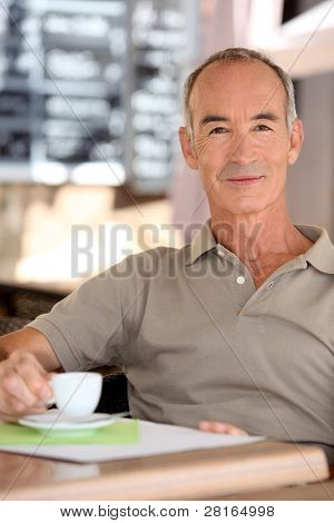 Senior man drinking a cup of espresso