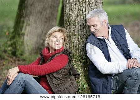 Middle-aged couple sat by tree