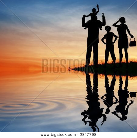 Family Silhouette On Sunset Sky. Water