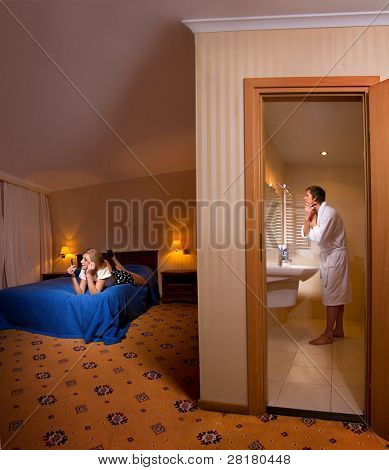Evening preparing of family for going out. Man shaving in the bathroom and his wife making up on bed