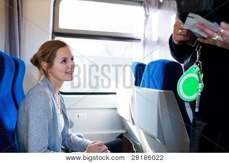 Young woman traveling by train, having her ticket checked by the train conductor