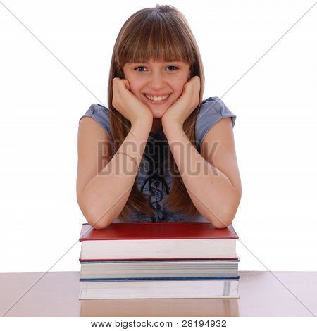 Girl Sits ? Table And Has Put Hands On Pile Of Books