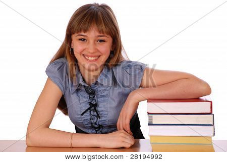 Girl Sits At Table And Has Put A Hand On Pile Of Books