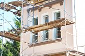 Painting And Plastering Exterior House Scaffolding Wall. Home Facade Insulation, Sctucco And Paintin poster