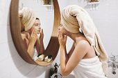 Young Happy Woman In Towel Applying Organic Face Mask And Looking At Round Mirror In Stylish Bathroo poster