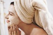 Skin Care Concept. Young Happy Woman In Towel Making Facial Massage With Organic Face Scrub Close Up poster