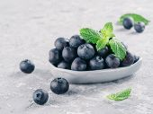 Fresh Ripe Blueberries In Small Trendy Plate. Blueberry In Gray Plate And Mint Leaves On Gray Concre poster