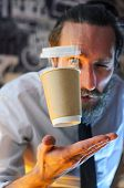 Levitating In The Air Paper Cup With Hot Coffee And Evaporation From It. Barista, A Bearded Young Ma poster