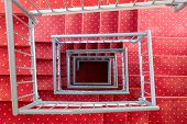 Top View In Symmetric Stairwell With Red Carpet And Steel Parapet poster