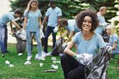 Volunteering, Charity And Clean Environment Concept. Happy Black Woman And Group Of Volunteers With  poster