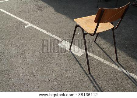 wooden schoolchair aligned on white basketball line