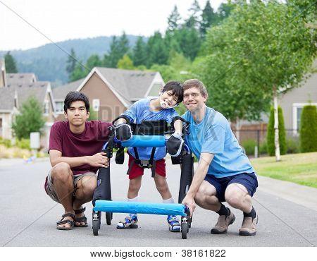 Niño con discapacidad en Walker rodeado de padre y hermano mayor