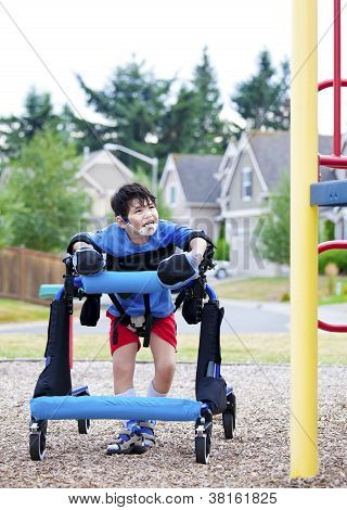 Disabled Boy In Walker Walking Up To A  Playground