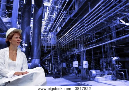 Attractive Female Engineer With Blueprints On With Industrial Pipelines On Background
