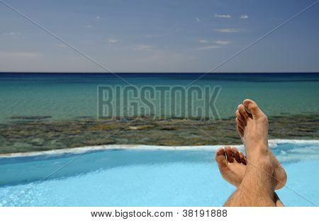 Picture of male legs over swimming pool and sea in the background