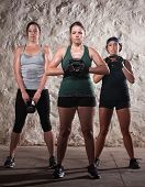 stock photo of boot camp  - Three strong women lifting kettlebell weights during boot camp workout - JPG