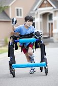 stock photo of street-walker  - Six year old disabled boy walking in walker down the street