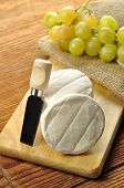 foto of tomas  - Italian tomino cheese on a wooden chopping board italian appetizer - JPG