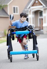 foto of street-walker  - Six year old disabled boy walking in walker down the street  - JPG